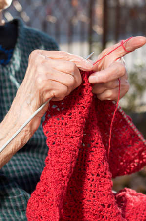 Senior woman hands knitting with red wool outdoors