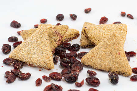 Integral triangle cookies with red raisins on white table