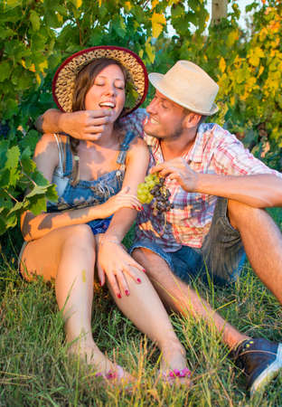 wine grower: Happy couple eating fresh grapes in vineyard