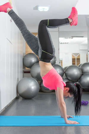 handstand: Young woman trying to handstand at the gym Stock Photo