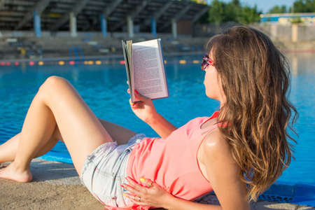 Girl reading a book by the pool. Summer vacation