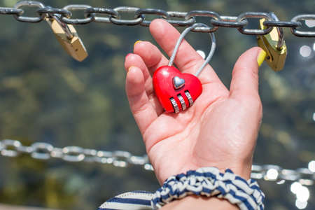 Woman hand holding a heart shaped padlock Stock Photo