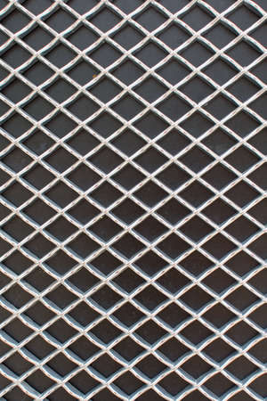 Photograph of rhombus metal grid pattern on black surface