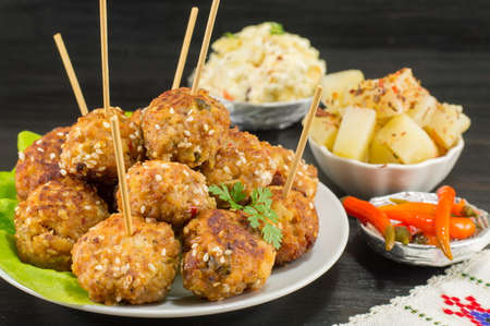 Meatballs on sticks in a plate with vegetables