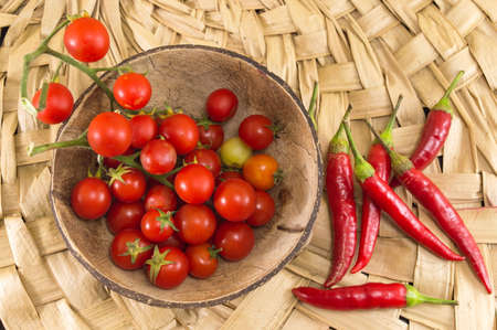 red peppers: Red peppers and fresh cherry tomato on wooden background