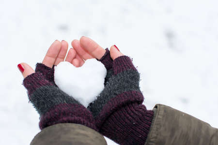 Woman hands holding heart shaped snowball outdoors