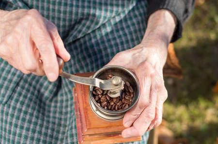 Senior woman grinding coffee on a vintage coffee grinder Stock Photo