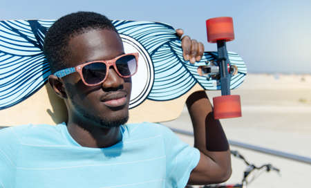 jamaican man: Happy young man outdoors holding his skateboard Stock Photo