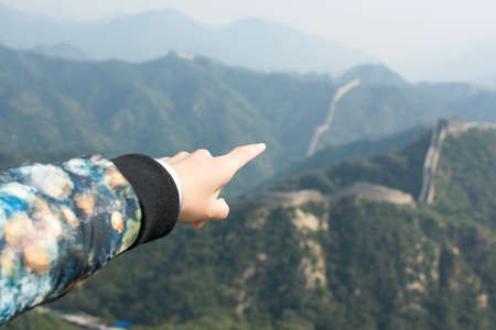 greatwall: Female hand pointing the Great Wall of China, lets go there