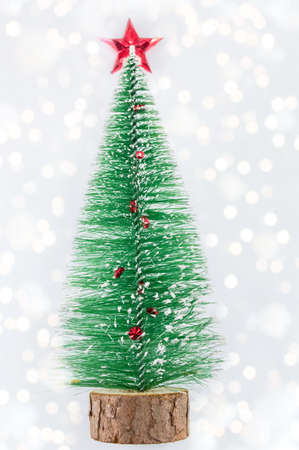 small christmas tree with a red star on top and bokeh