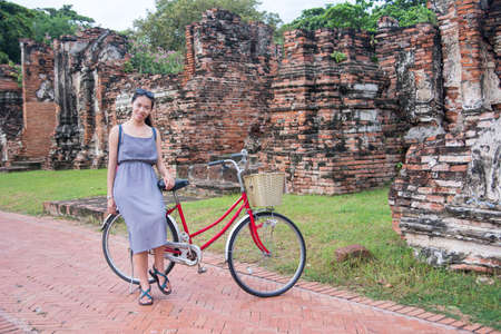 museum visit: Girl with bicycle in front of ancient Ayutthaya Kingdom in Thailand
