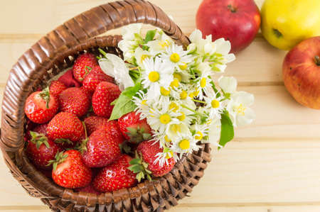chamomile flower: strawberries and chamomile in a woven wooden basket