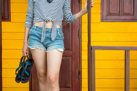 Girl walking out of the beach house holding sandals