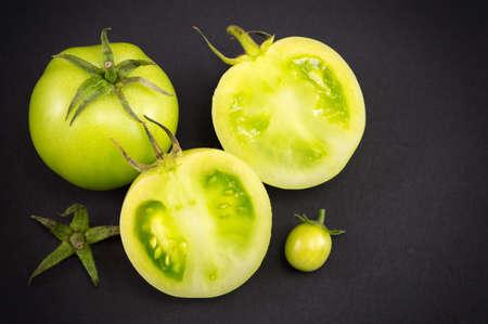 Sliced raw green tomatoes on dark backgeround