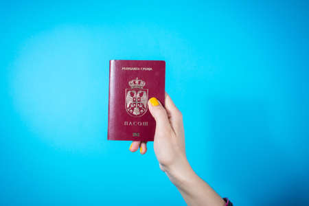 NIS, SERBIA - MAY 18, 2016: Woman hand holding Serbian passport against blue background