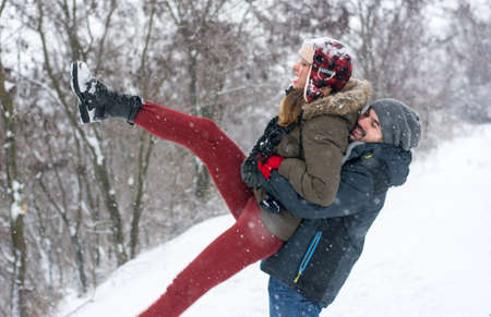 having fun in winter time: Crazy couple having fun in a snow covered park