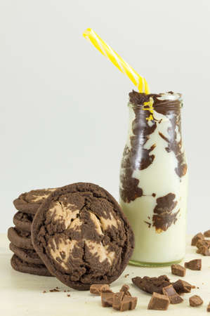 vacas lecheras: Chocolate chip brown cookies and milk on a wooden table Foto de archivo
