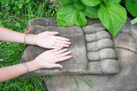 Female hand praying on top of big Buddha hand in Ayothaya Imagens