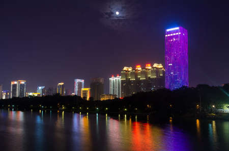 NANNING, CHINA - SEPTEMBER 18: View at the modern business city area with high buildings reflecting in the Nanhu lake. Nanning is the capital city of Guangxi province