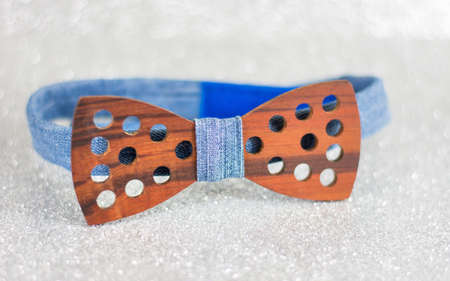 Wooden bow tie on silver shiny background