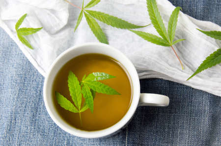 Cannabis tea and marijuana leaves top view Banco de Imagens