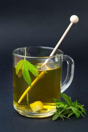 Marijuana herbal tea and green cannabis leaves Stock Photo