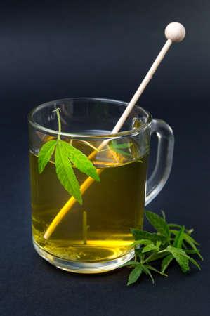 Marihuanathee en groene cannabisbladeren op zwart