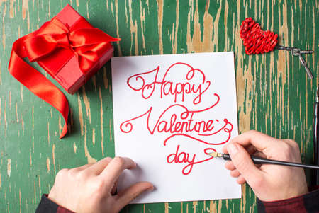 Man writing a Valentines day card and preparing a present