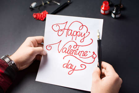 male hands writing a Valentines day card calligraphy