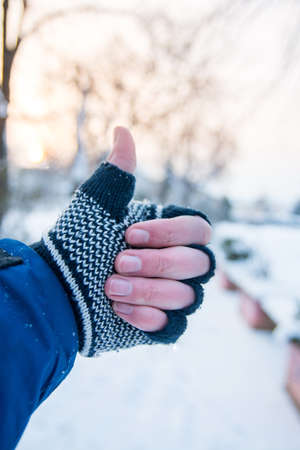 Male hand showing thumbs up in winter gloves outdoors
