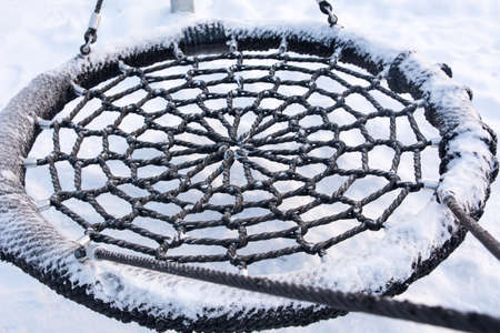 Close up of a frozen swing seat in the park