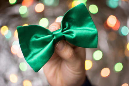 Male hand holding a green bow tie. St Patricks day preparation Stockfoto