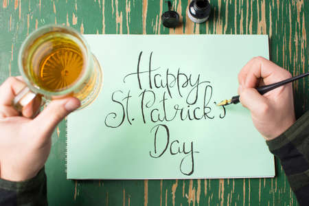 Man having a beer with Happy St Patrick day calligraphy card Stock Photo