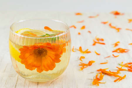 pot marigold: marigold flower herbal tea with lemon slices in a glass