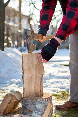 winter wood: Man chopping firewood in the front yard