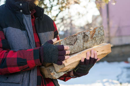 front yard: Man carrying firewood in the front yard Stock Photo