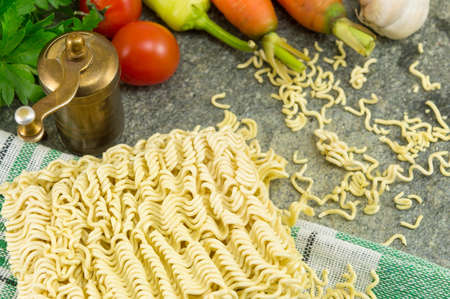 square of uncooked noodles with carrots and parsley Stock Photo