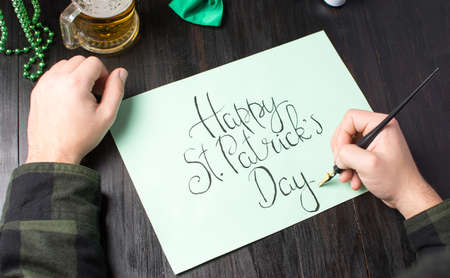 Male hands writing a Happy St Patrick day calligraphy card