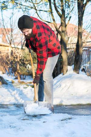 shoveling: bearded man shoveling snow in a checked shirt Stock Photo