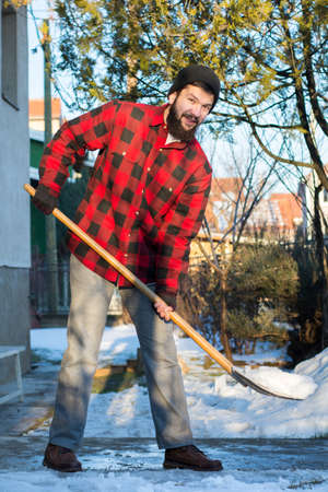 bearded man shoveling snow in a checked shirt Stock Photo