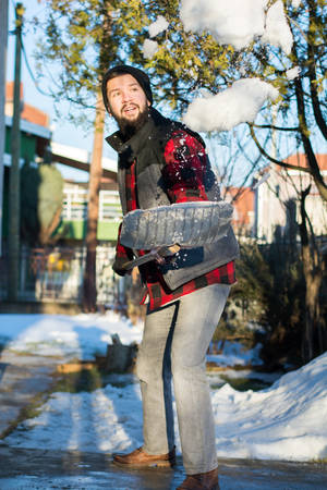 shoveling: bearded man shoveling snow wearing a shirt and a west Stock Photo