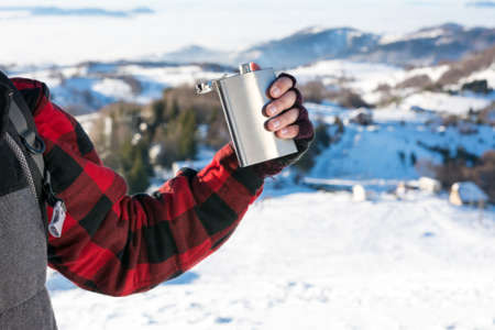Male hand holding hip flask on a snowy mountain top