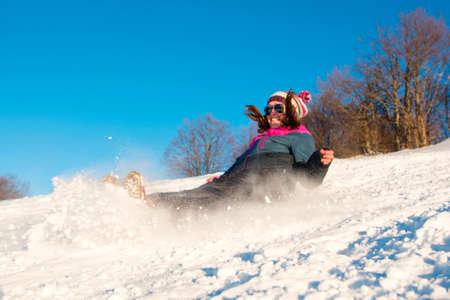 Girl falling down on the snowy mountain Stock Photo