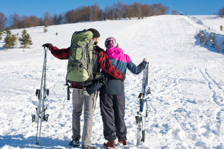 Couple with skis on the snow covered mountain