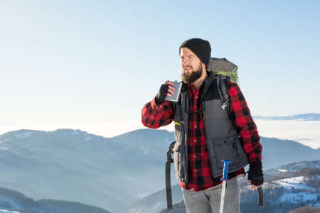 Man drinking from a hip flask on winter hiking trip