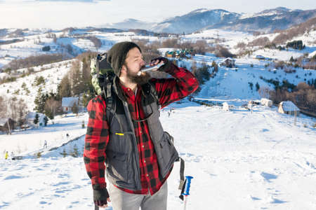 Man drinking from a hip flask on  snowy mountain top