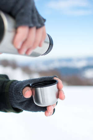 Man using a thermos in on a snowy mountain