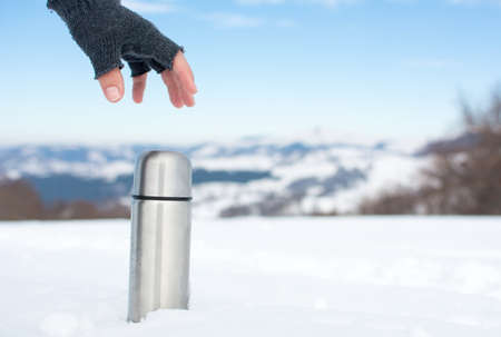 Man holding a thermos in on a snowy mountain