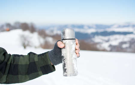 Man holding a thermos on a hiking trip