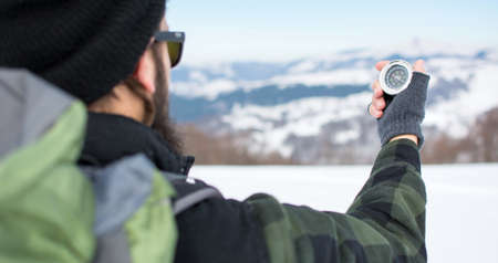 Hipster man using a compass on a snowy mountain